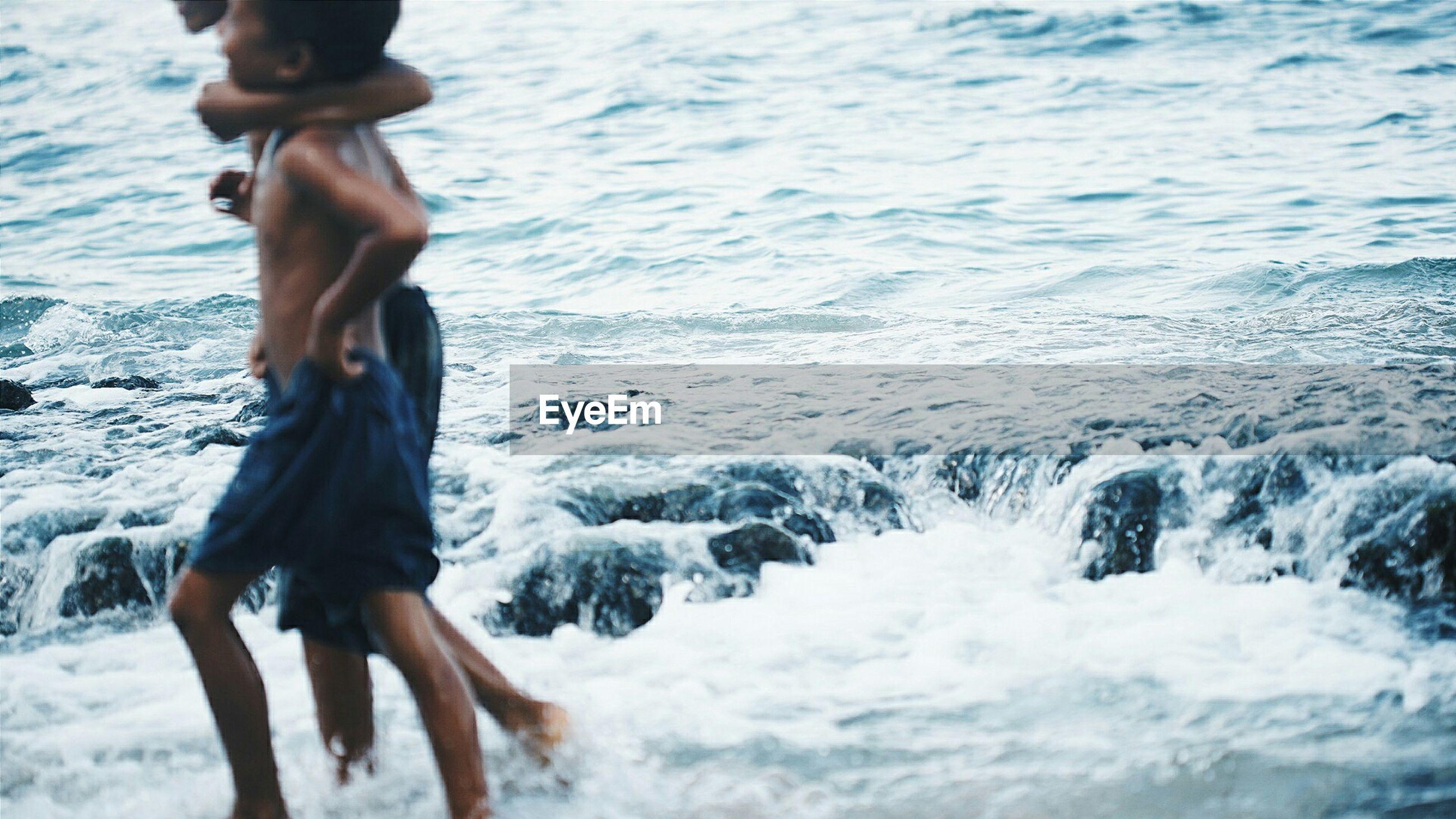 Boys walking on shore