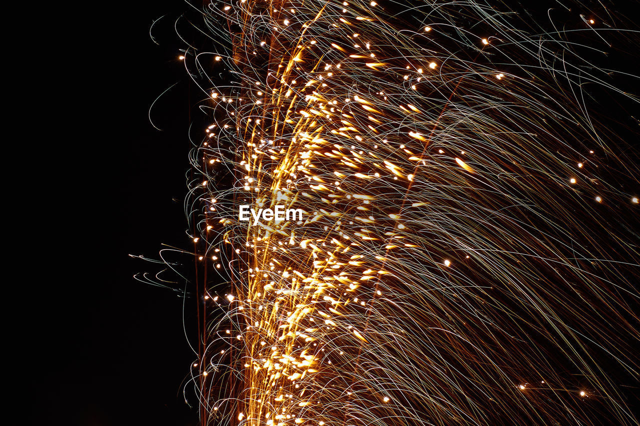 sparks, night, firework - man made object, long exposure, firework display, glowing, motion, celebration, low angle view, illuminated, exploding, no people, black background, sparkler, outdoors, sky, close-up