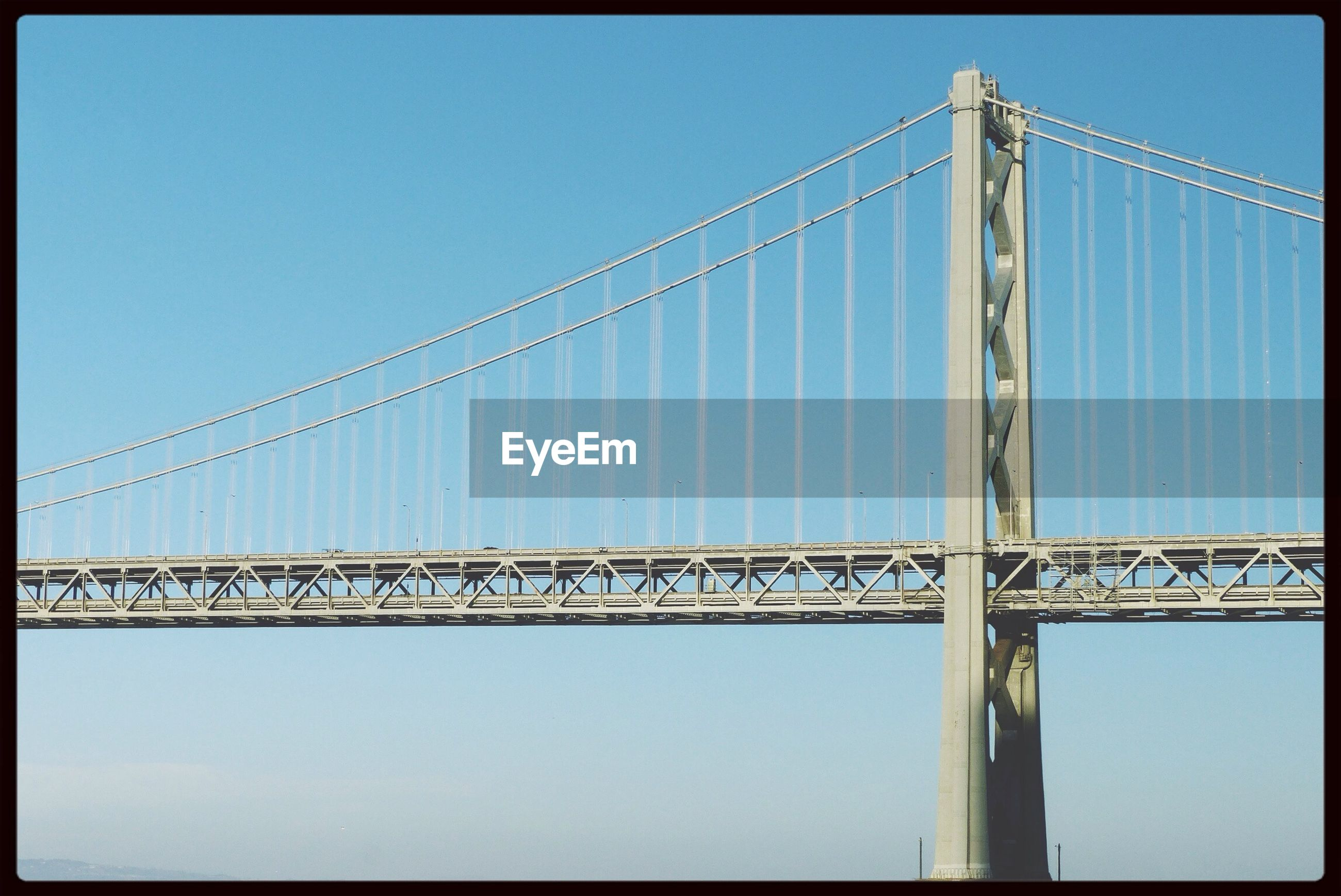 clear sky, low angle view, transfer print, connection, blue, built structure, architecture, auto post production filter, copy space, power line, sky, day, outdoors, bridge - man made structure, electricity pylon, cable, no people, engineering, metal, sunlight