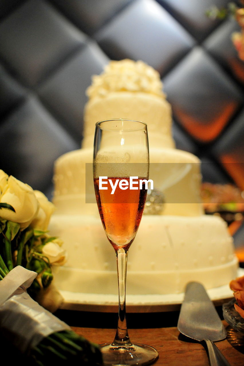Close-Up Of Drink In Champagne Flute By Cake At Table