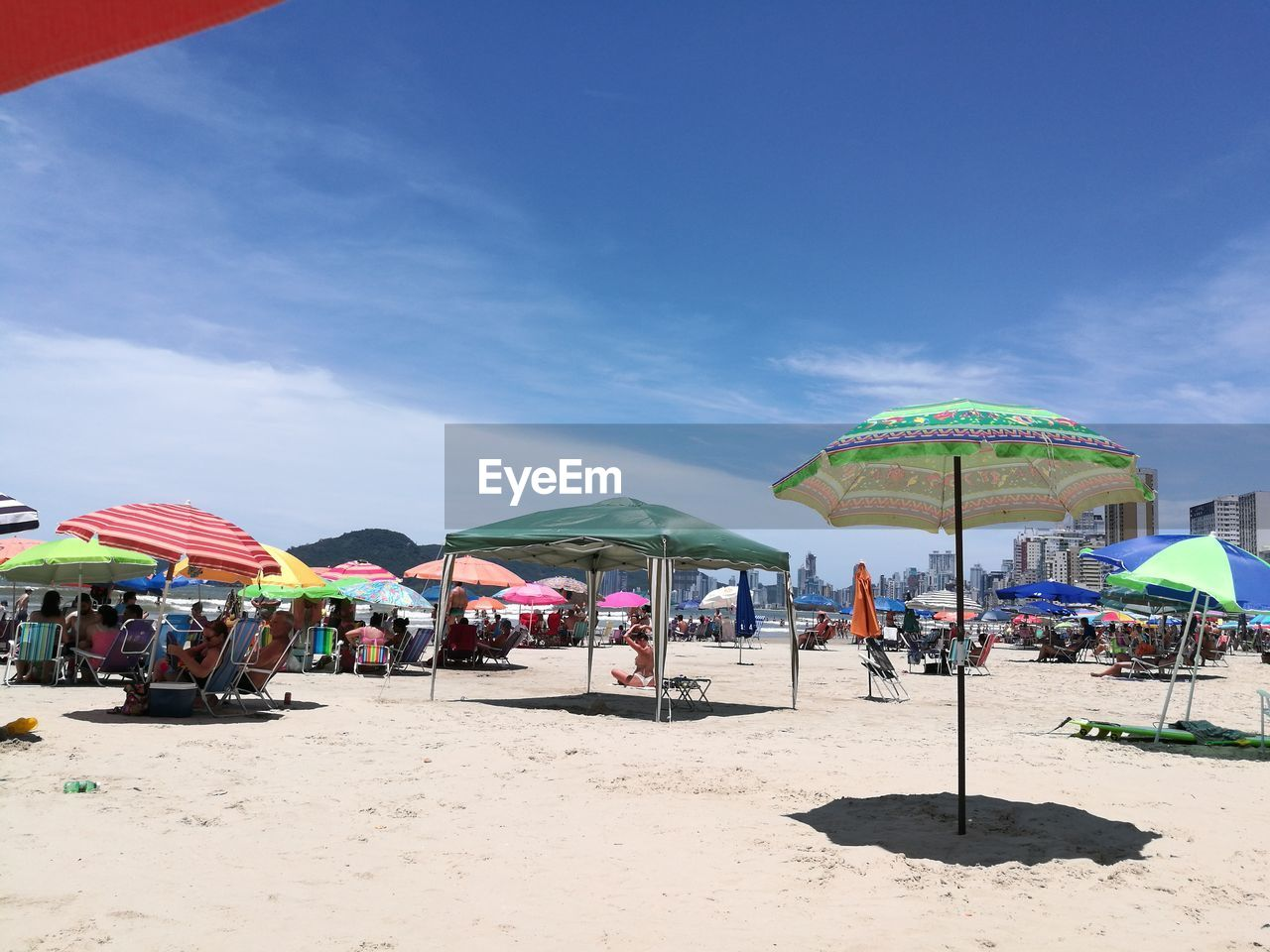 beach, sand, beach umbrella, summer, vacations, outdoors, large group of people, canopy, day, enjoyment, nature, leisure activity, sunlight, sky, multi colored, real people, fun, weekend activities, relaxation, blue, women, group of people, sea, men, people