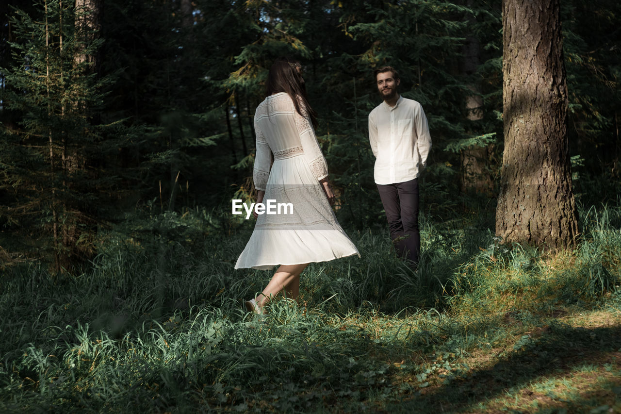 Smiling couple standing in forest