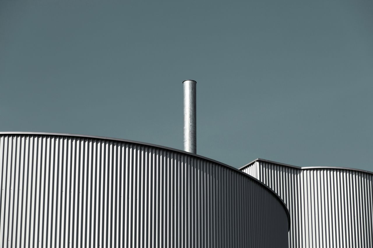 Low angle view of silos against clear blue sky