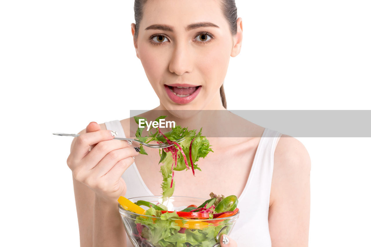 Portrait of young woman eating salad against white background