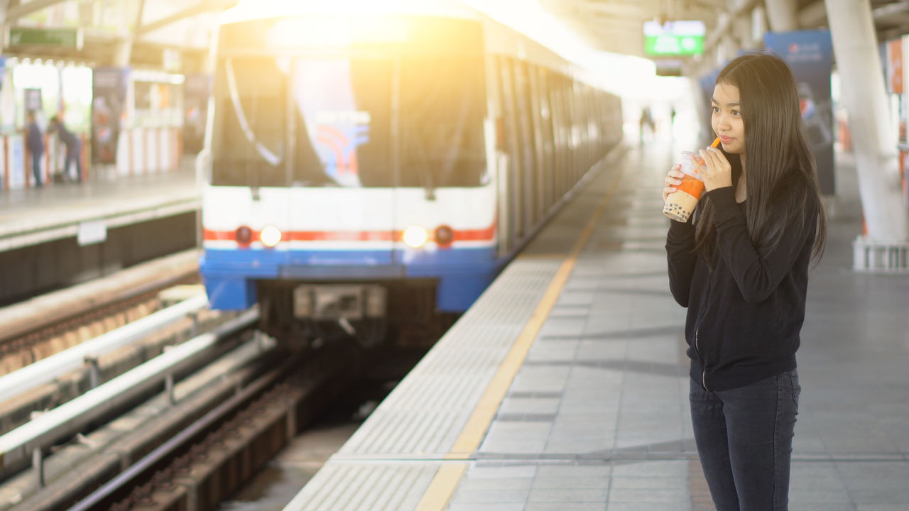 Girl drinking while standing at railroad station platform