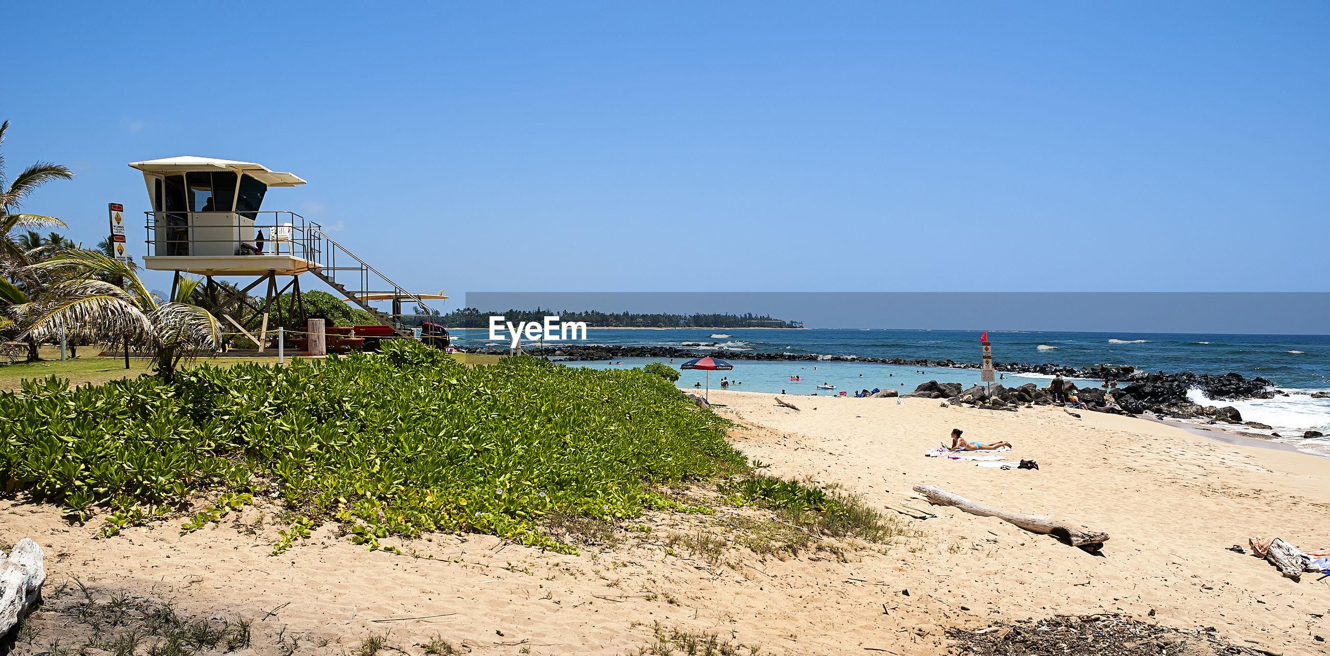 Lifeguard hut at beach in hawaiian paradise park against clear sky