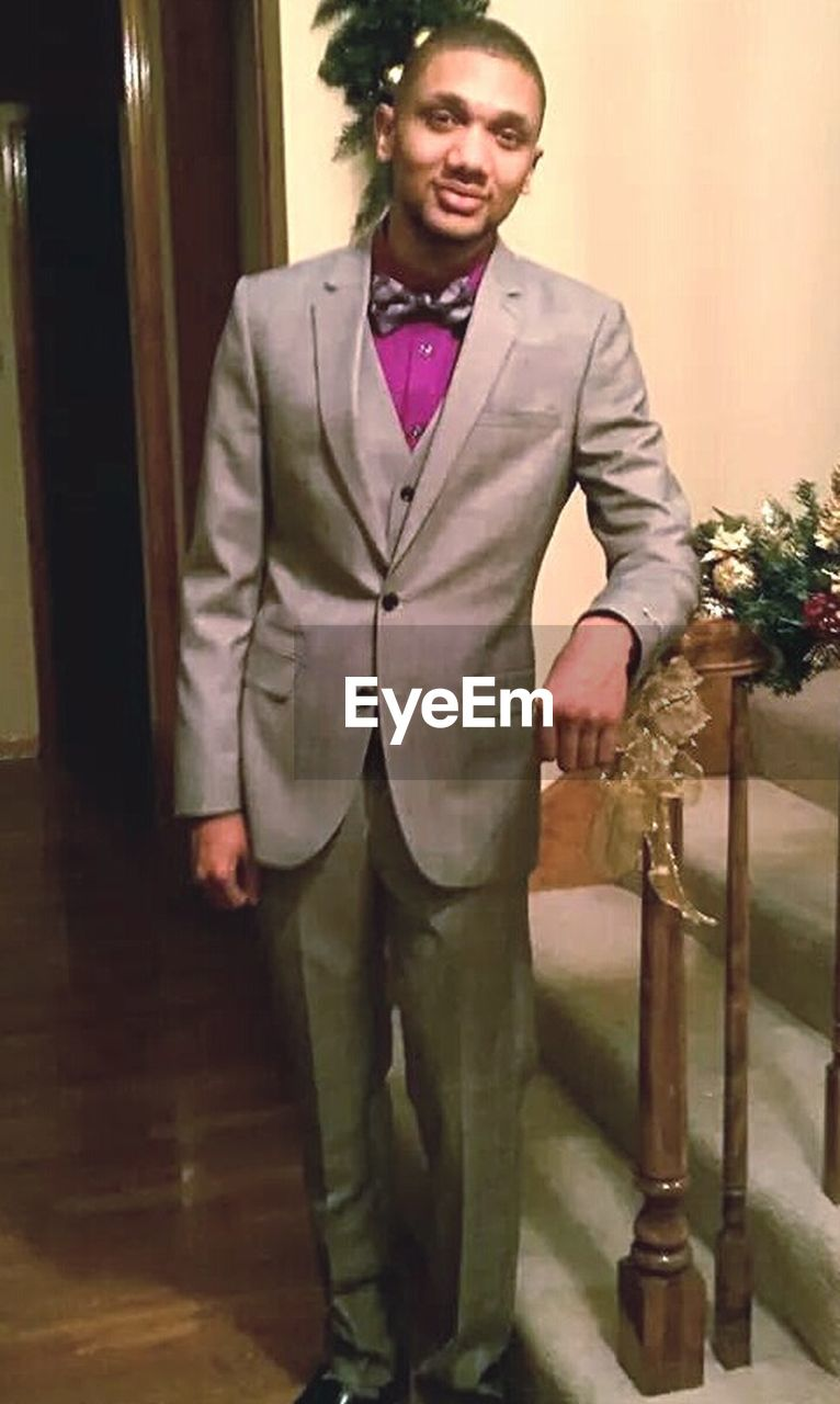 one man only, portrait, only men, one person, looking at camera, adults only, adult, standing, front view, indoors, people, men, well-dressed, full length, smiling, suit, happiness, cheerful, one young man only, young adult, day
