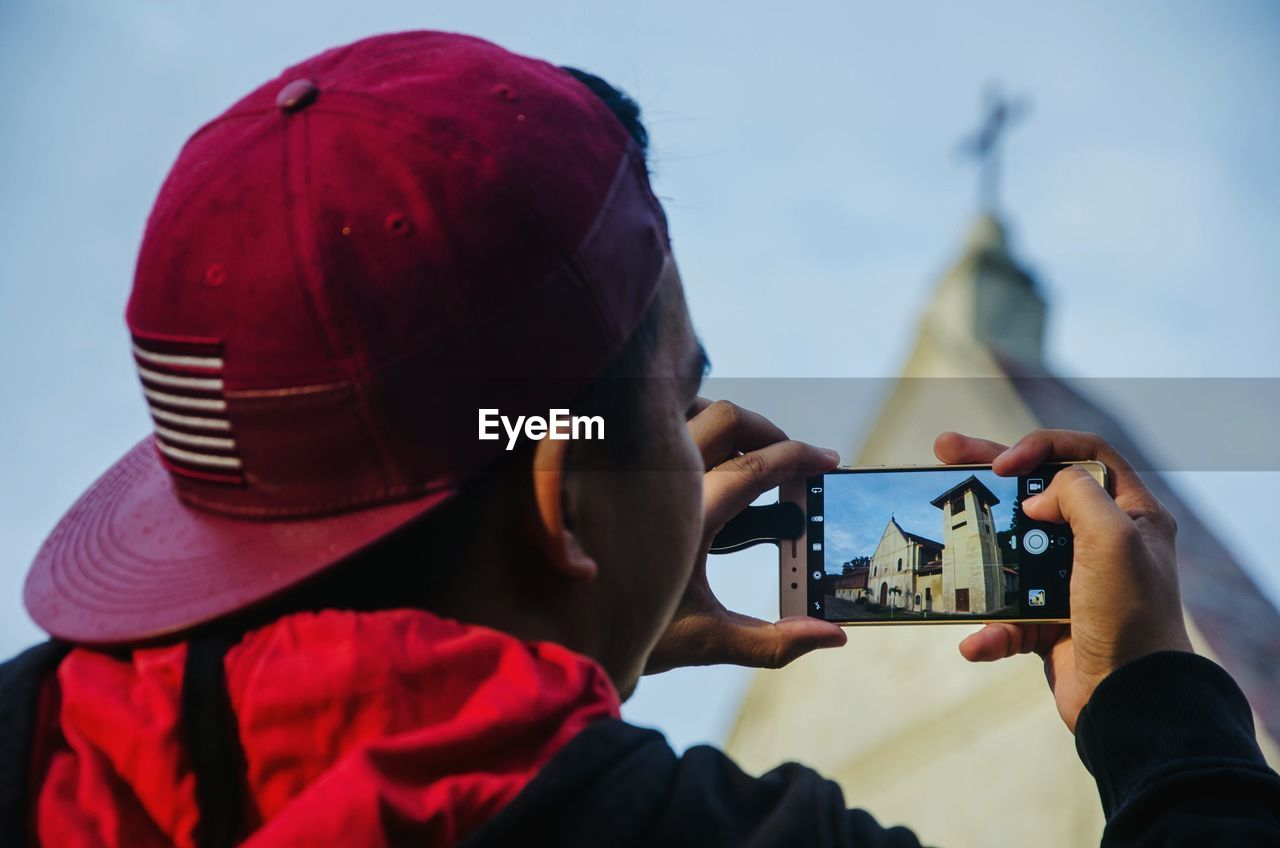 Rear View Of Man Photographing Church Through Smart Phone Against Sky