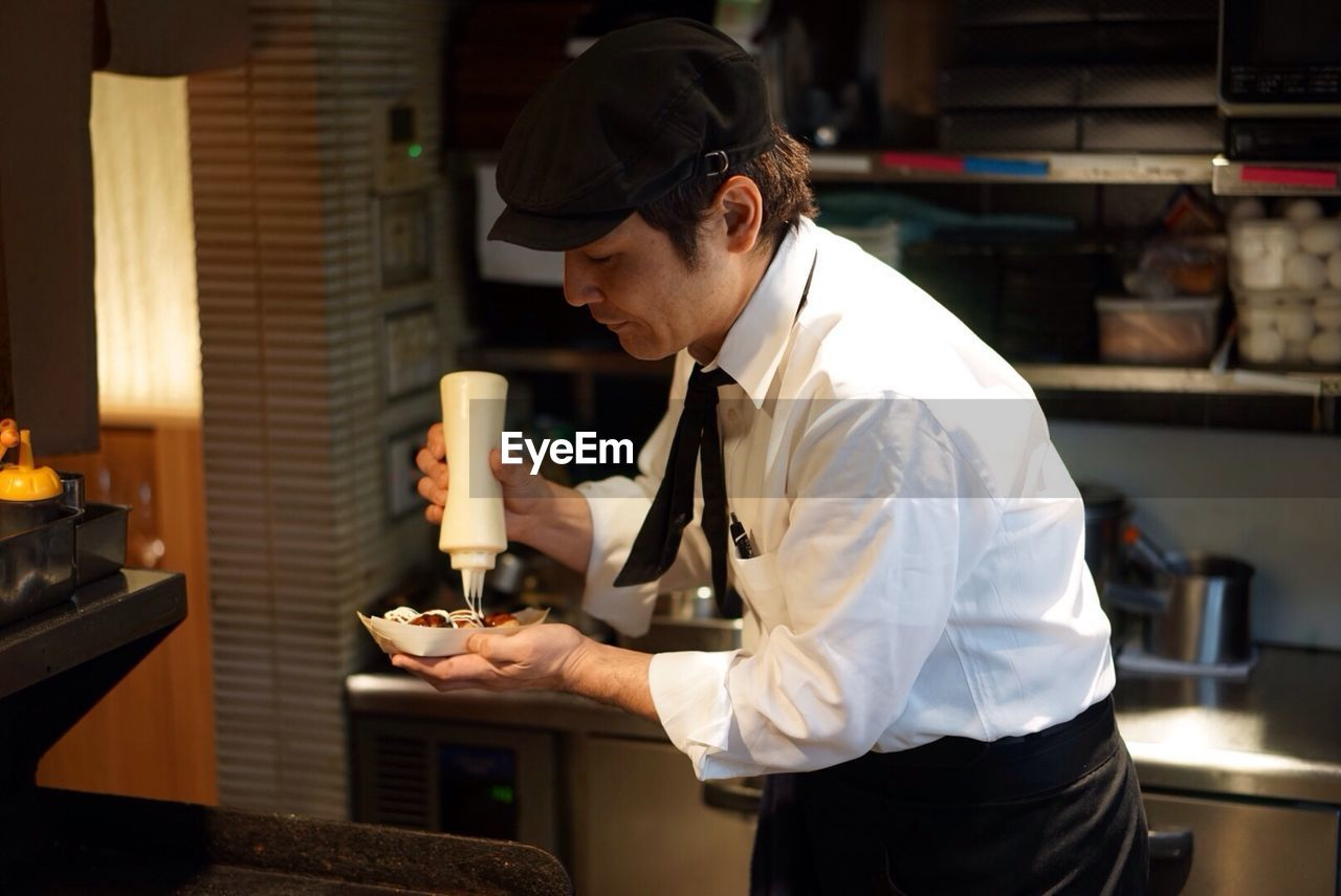 Chef Preparing Takoyaki In Kitchen
