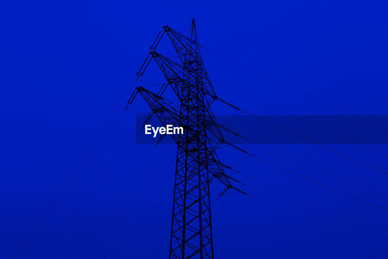 cable, electricity, power line, technology, power supply, electricity pylon, connection, low angle view, blue, fuel and power generation, sky, no people, nature, tall - high, clear sky, metal, outdoors, built structure, lighting equipment, architecture, complexity, purple, electrical equipment, electrical component