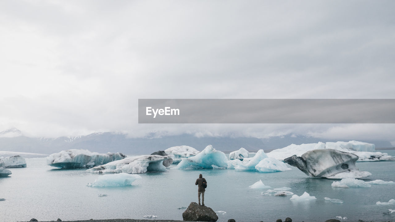 Rear View Of Man Standing On Rock Against Icebergs In Sea Against Sky