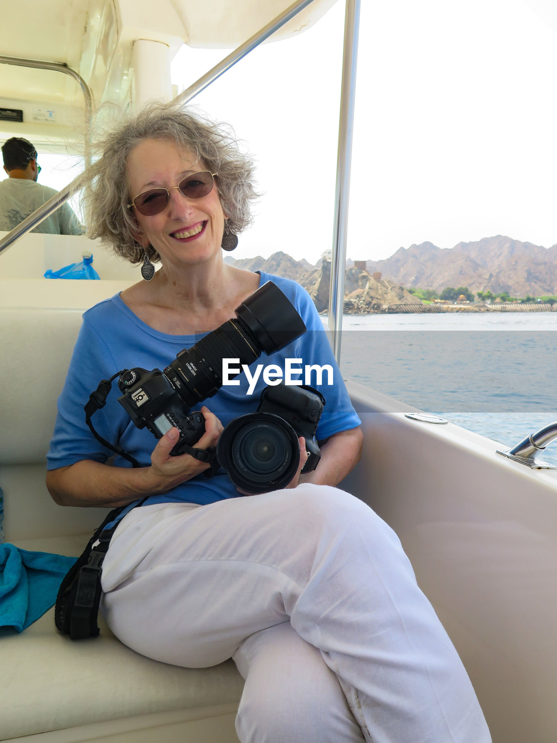 Portrait of smiling senior woman holding digital camera while sitting in boat