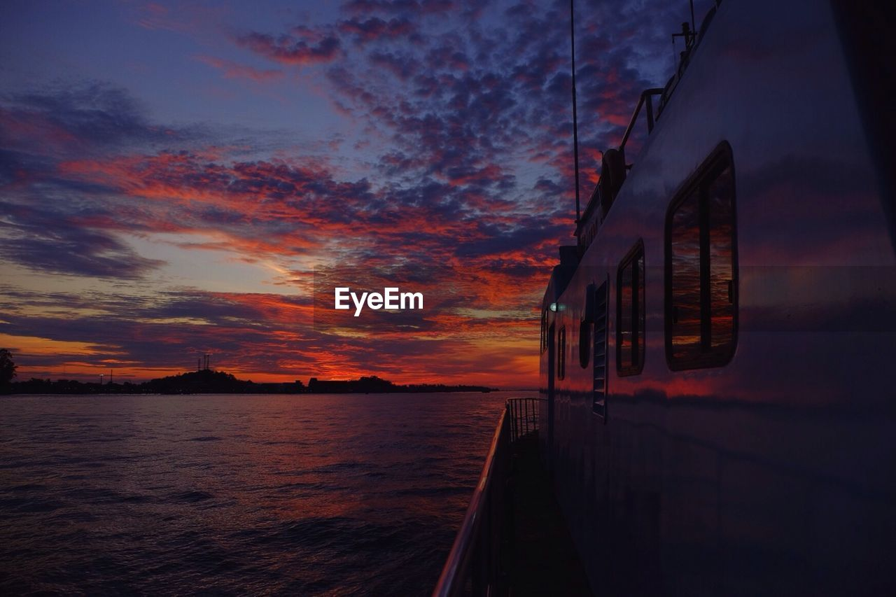 Scenic View Of Boat Deck Against Cloudy Sky At Sunset