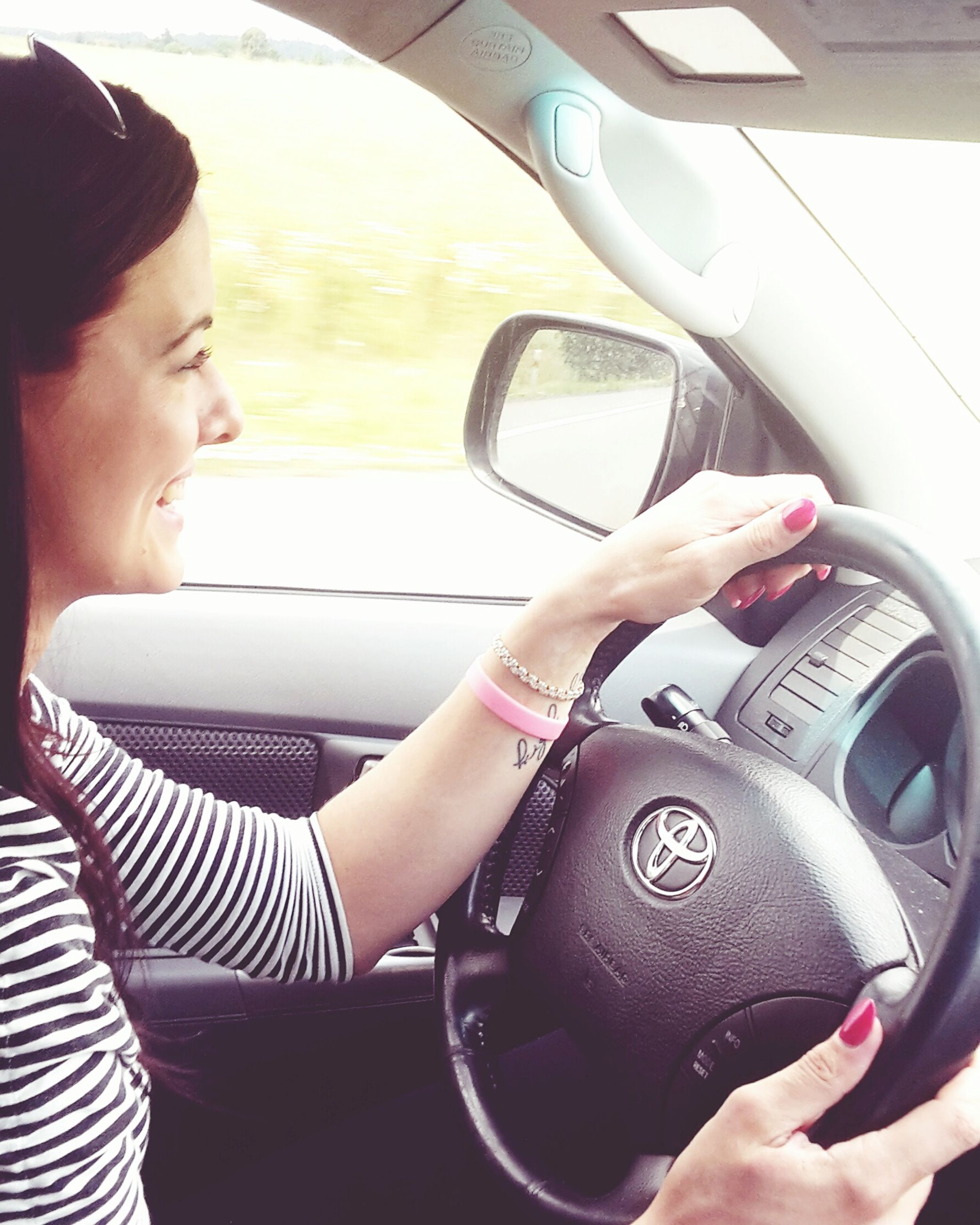 lifestyles, leisure activity, person, indoors, holding, young adult, sitting, technology, casual clothing, wireless technology, smart phone, vehicle interior, young women, communication, mobile phone, front view