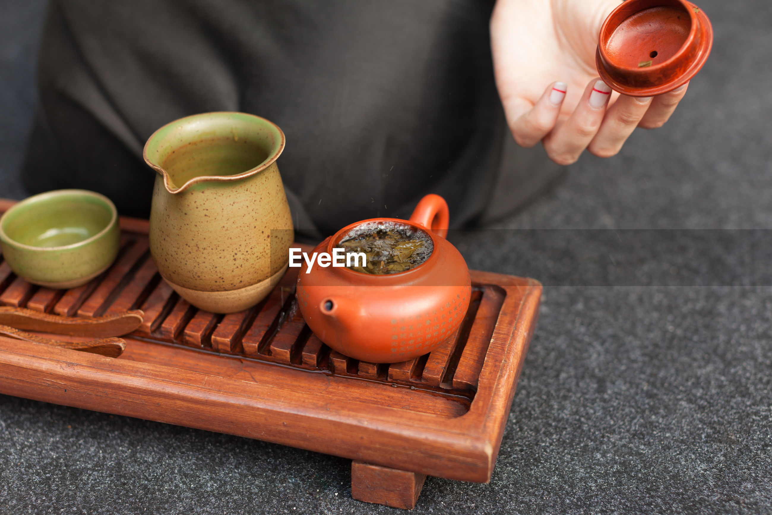 Close-up of hand holding teapot lid while sitting at floor