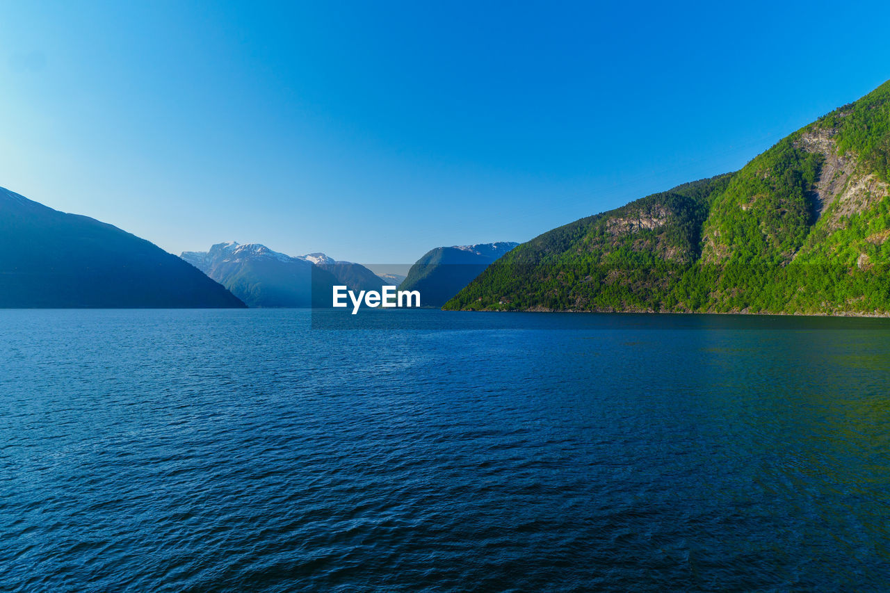 water, scenics - nature, beauty in nature, sky, mountain, tranquil scene, waterfront, tranquility, sea, blue, day, idyllic, mountain range, clear sky, no people, nature, non-urban scene, copy space, outdoors