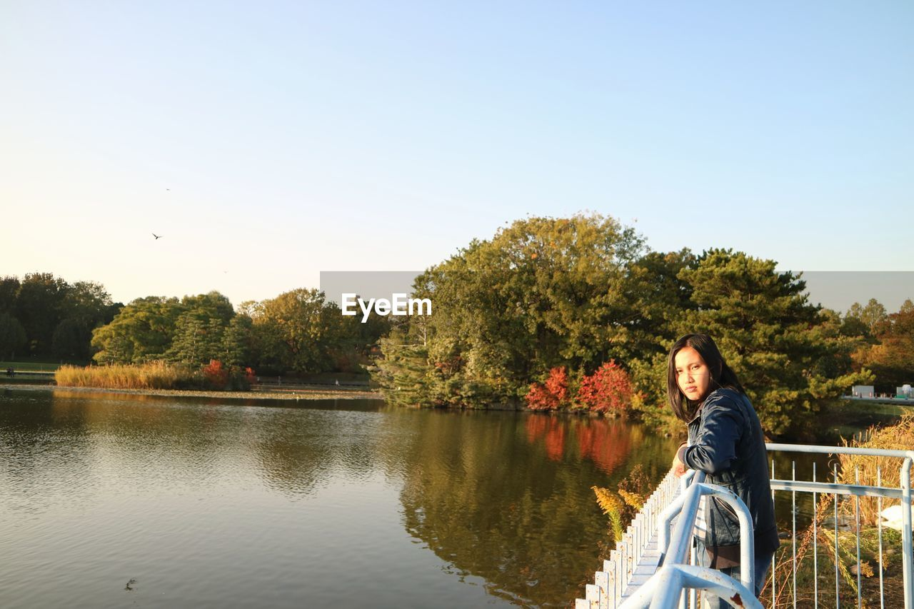 Portrait Of Young Woman Standing By Railing Over Lake Against Clear Sky