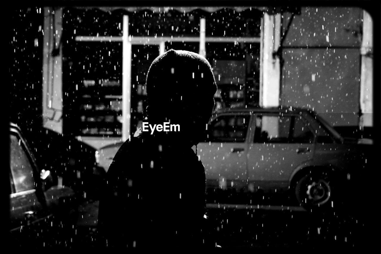 rain, real people, car, land vehicle, wet, transportation, weather, rear view, mode of transport, night, lifestyles, one person, built structure, raindrop, outdoors, building exterior, architecture, women, water, snowing, car wash, window washer, adult, people