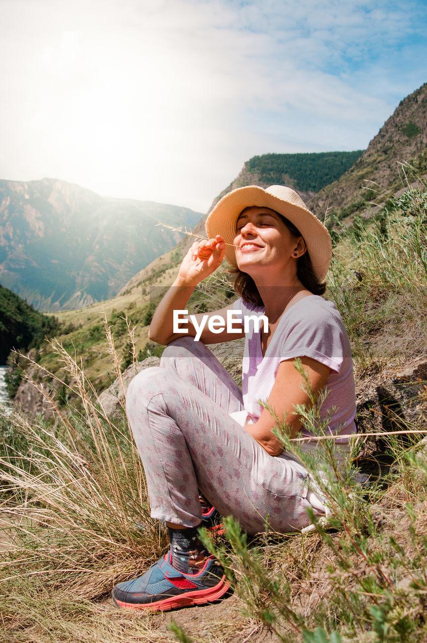 Full Length Of Woman Sitting On Landscape Against Mountain Range