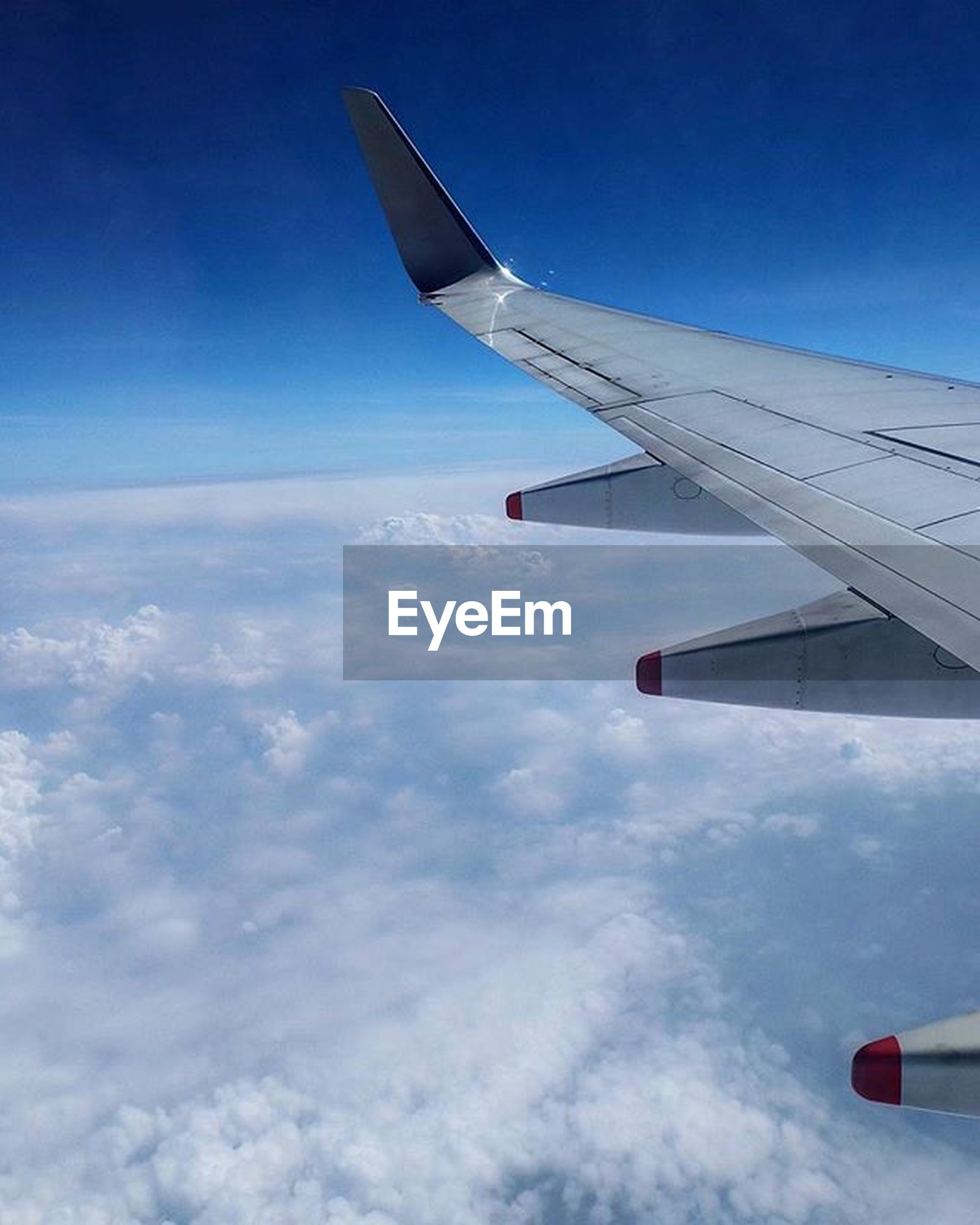 airplane, aircraft wing, flying, air vehicle, transportation, mode of transport, part of, cropped, mid-air, aerial view, travel, journey, sky, on the move, blue, public transportation, scenics, airplane wing, landscape, beauty in nature