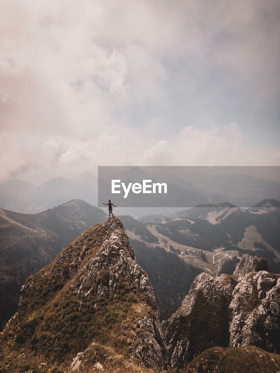 Woman Standing On Mountain Peak Against Sky