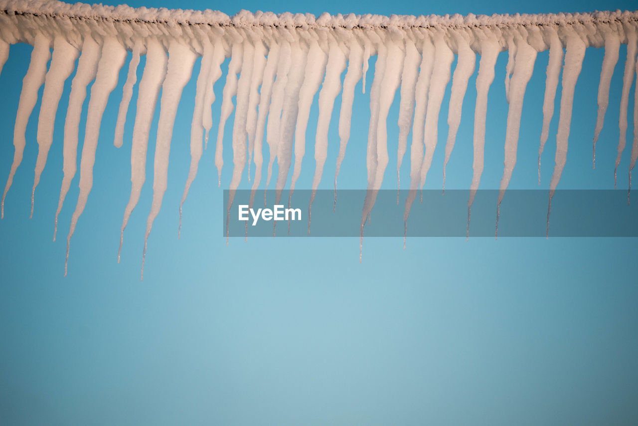 Close-Up Of Icicles Against Clear Blue Sky