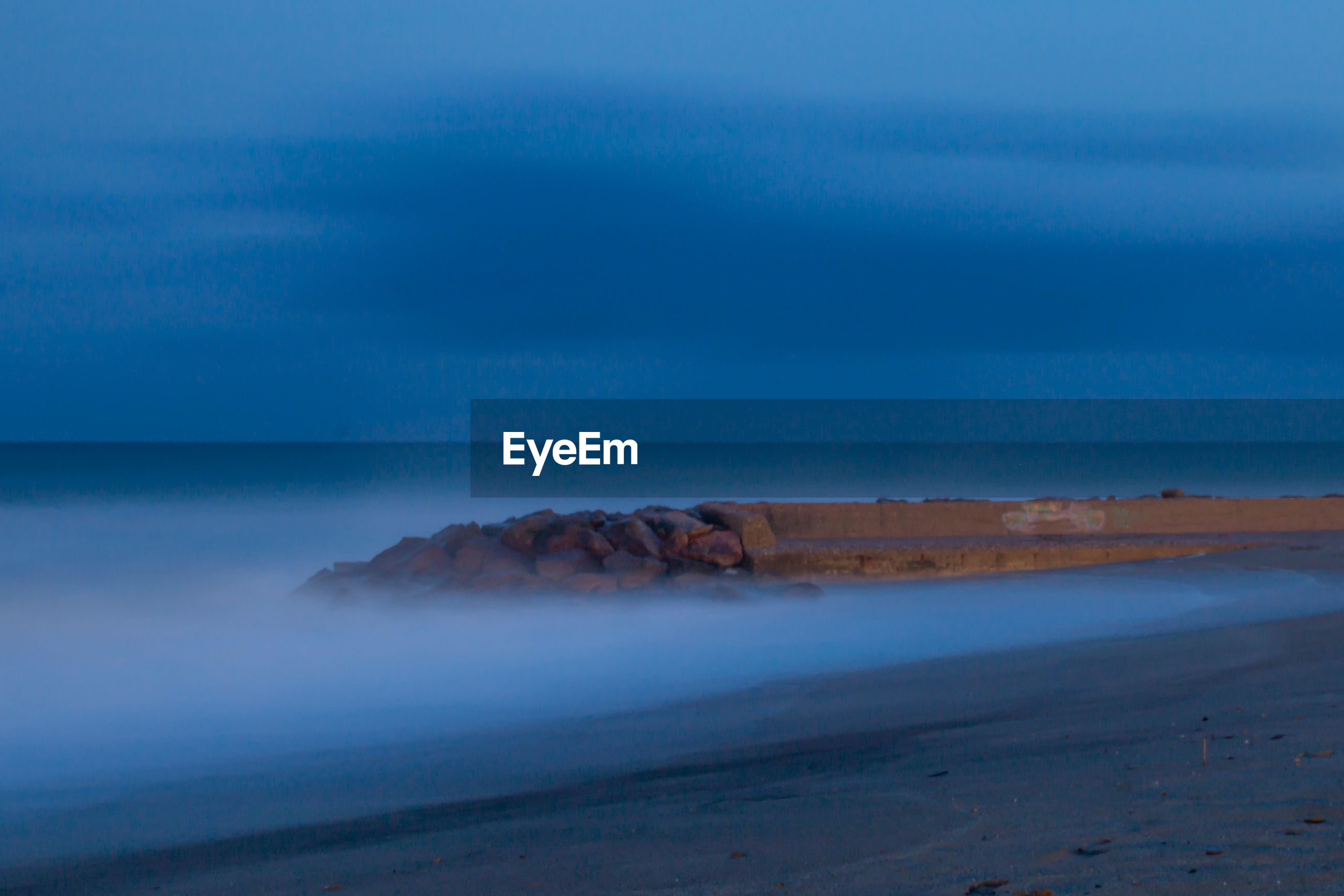SEA BY BEACH AGAINST SKY