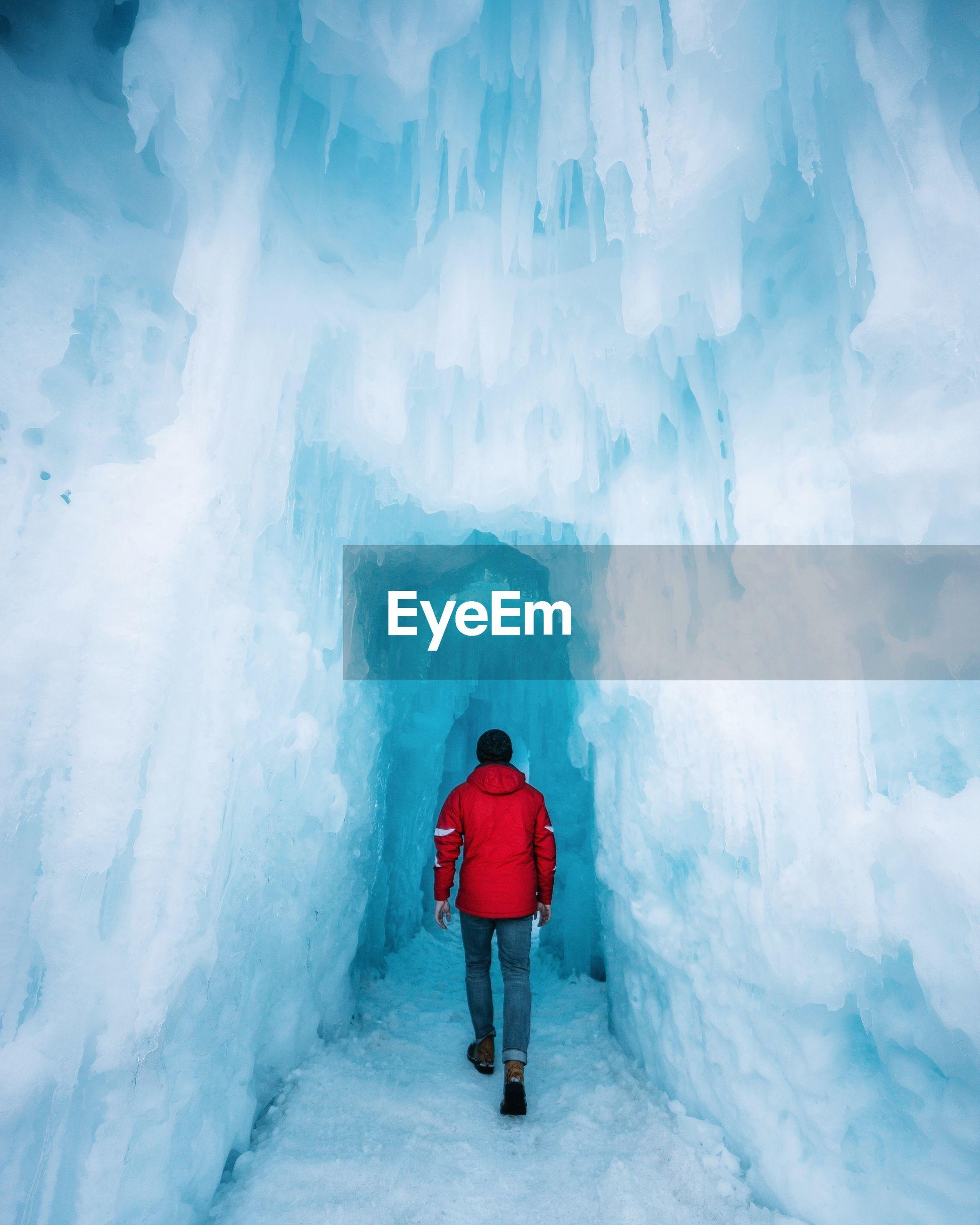 Rear view of man walking in glacier