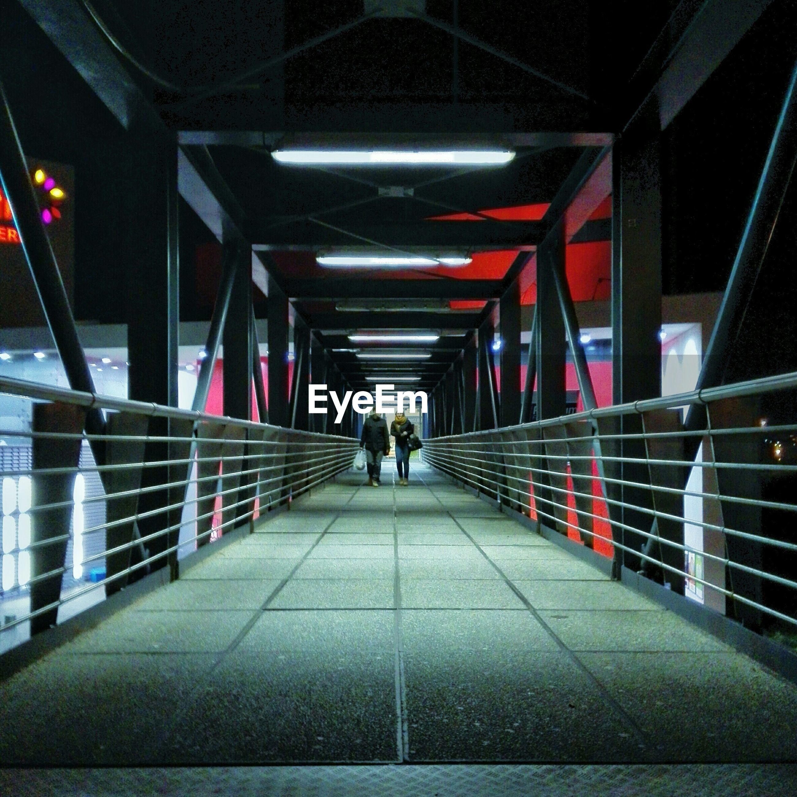 Couple walking at illuminated footbridge