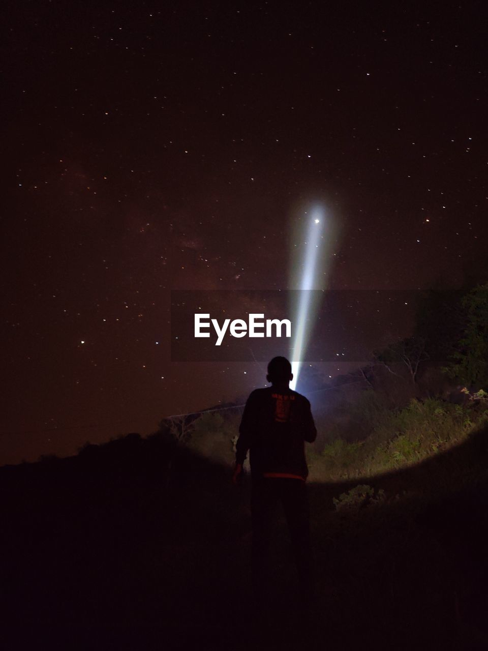 Rear view of silhouette hiker with flashlight watching stars during night