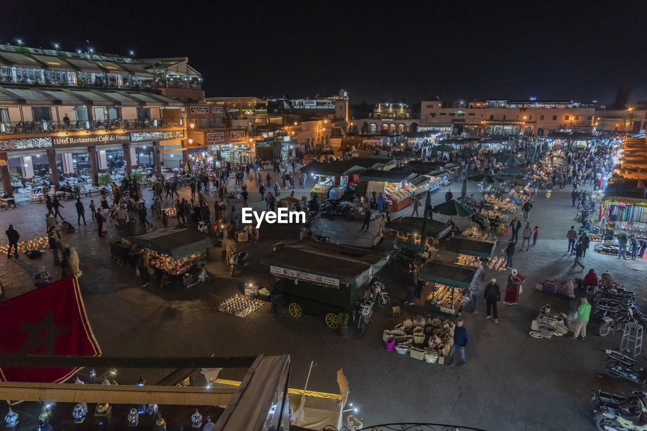 Crowd at illuminated night market in city