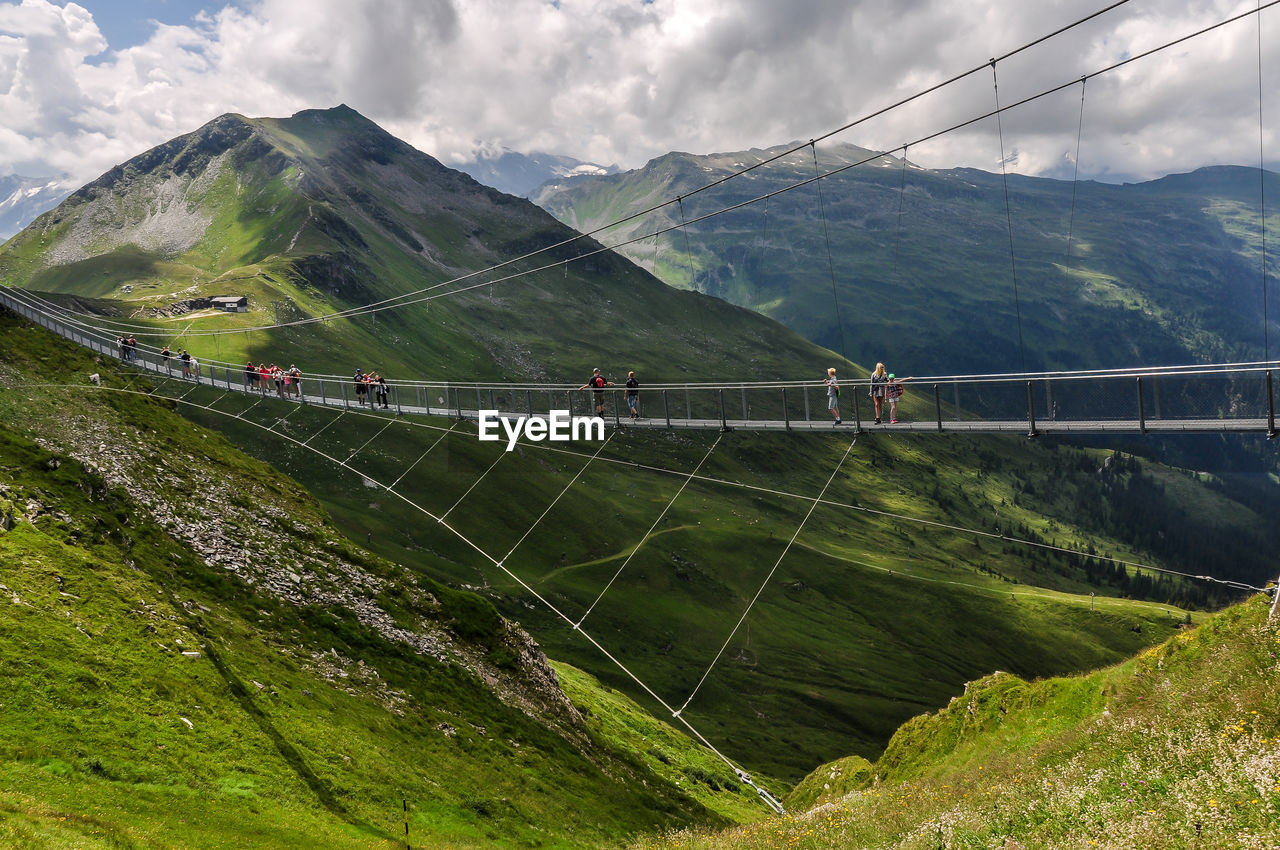 mountain, sky, cloud - sky, nature, transportation, beauty in nature, scenics - nature, connection, environment, day, green color, mountain range, bridge, built structure, bridge - man made structure, landscape, non-urban scene, water, group of people, road, outdoors