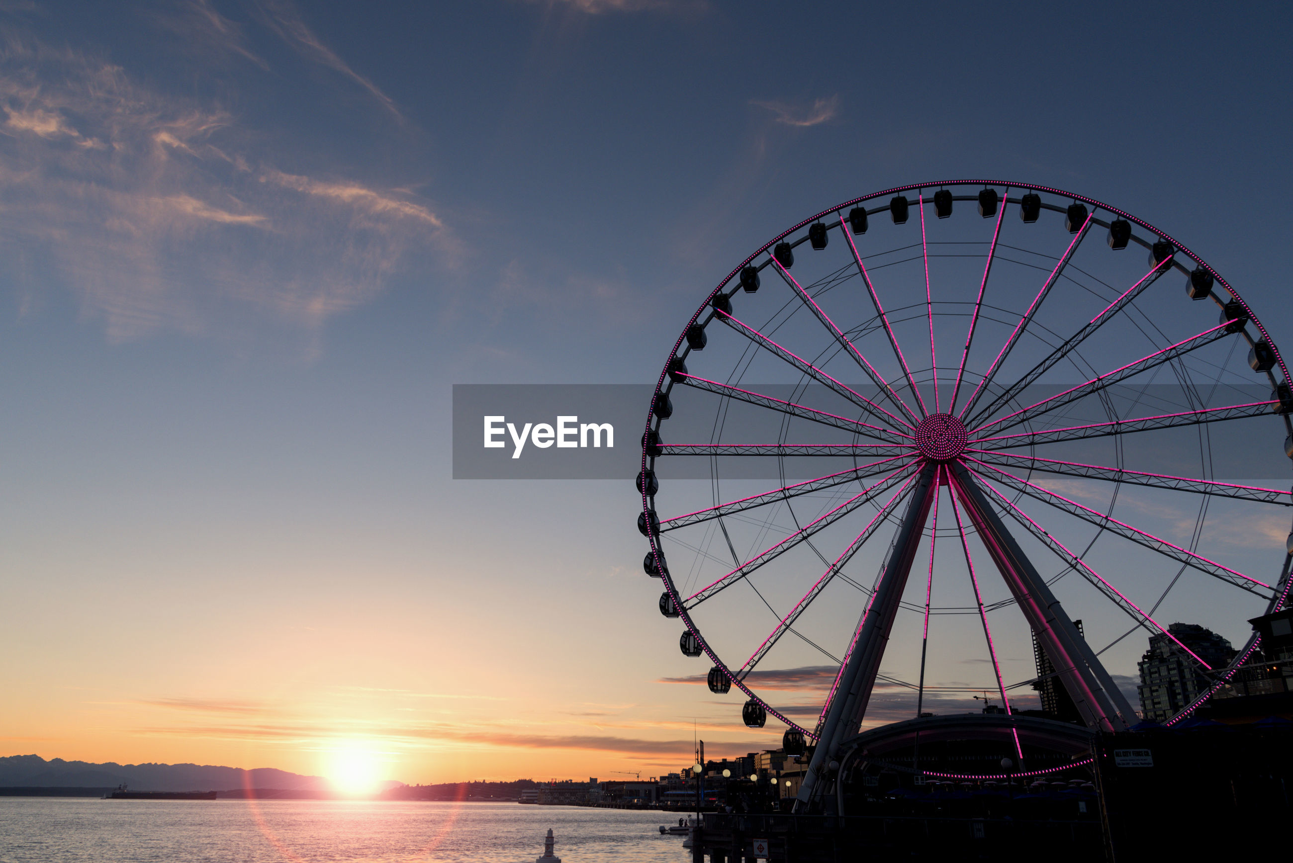 Low angle view of illuminated ferris wheel by sea against sky during sunset