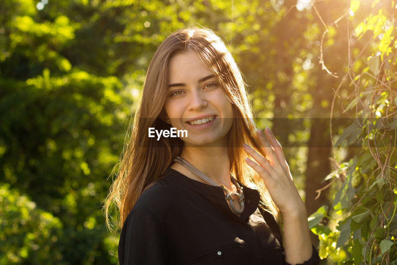 smiling, happiness, portrait, young women, one person, real people, young adult, hair, beauty, plant, leisure activity, emotion, lifestyles, beautiful woman, sunlight, women, looking at camera, tree, long hair, hairstyle, outdoors