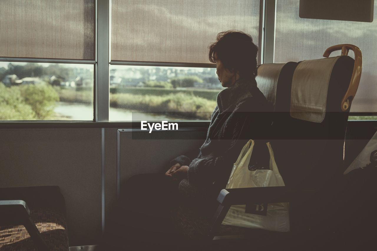 window, sitting, real people, mode of transportation, seat, one person, train, transparent, transportation, rail transportation, vehicle interior, train - vehicle, glass - material, travel, public transportation, lifestyles, land vehicle, indoors, leisure activity, men, contemplation