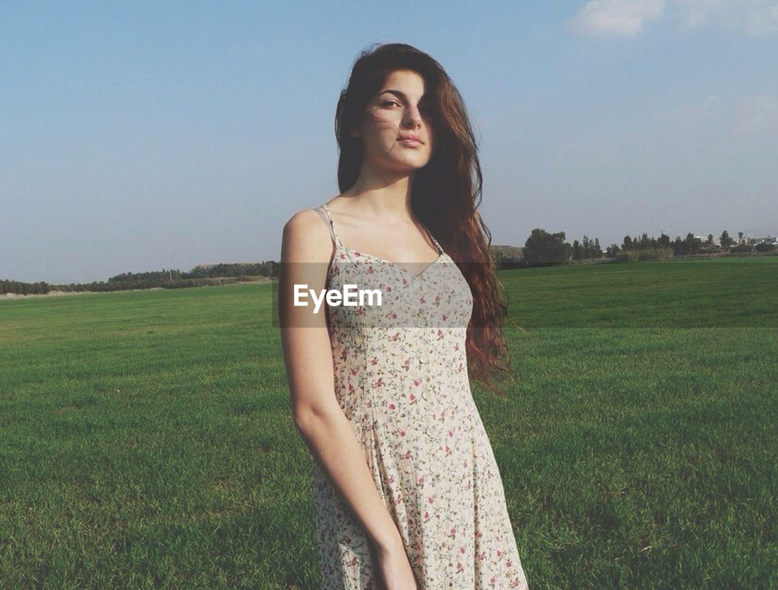 grass, young adult, young women, lifestyles, person, field, casual clothing, grassy, leisure activity, portrait, standing, looking at camera, front view, long hair, sky, three quarter length, nature