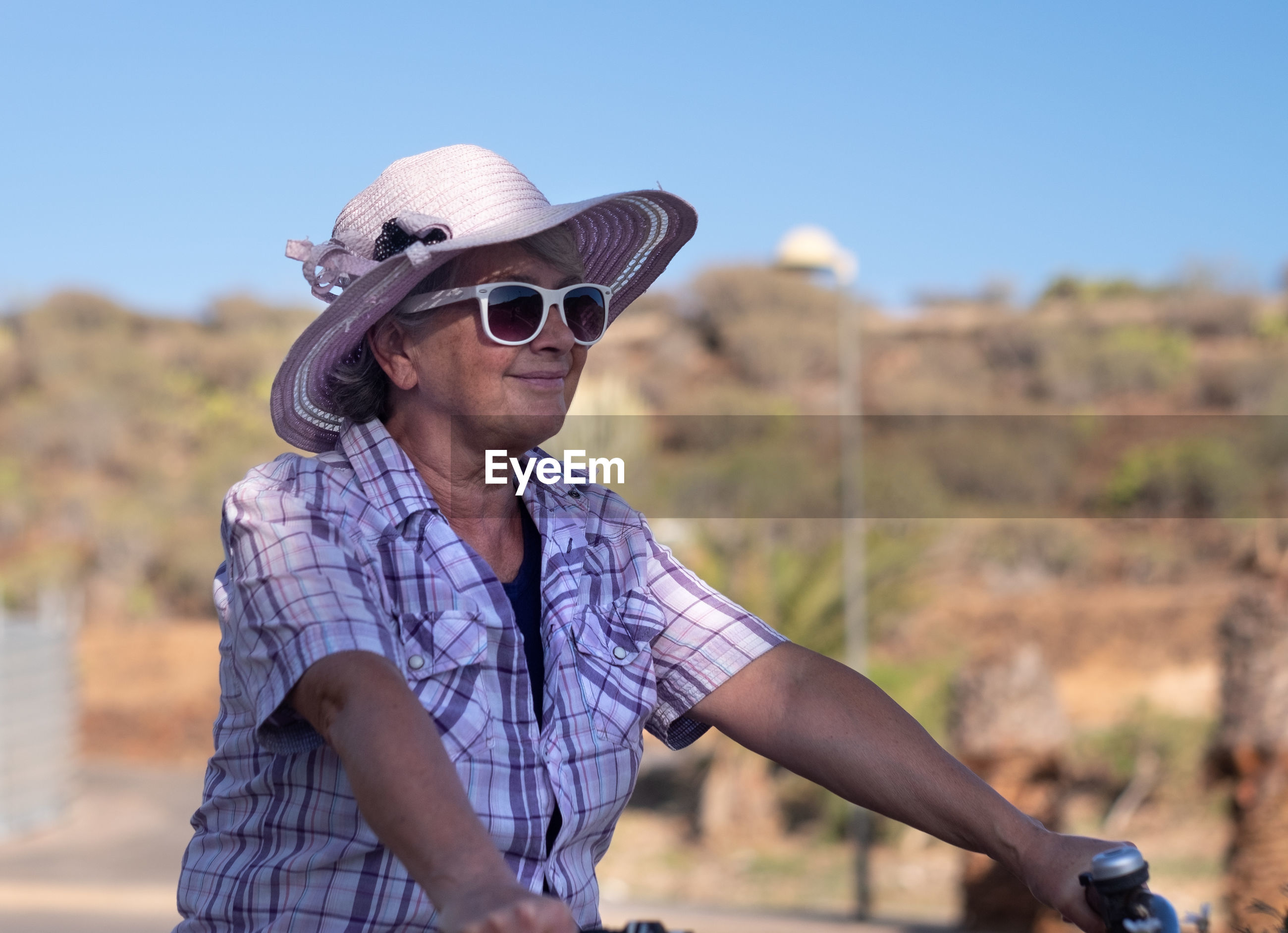 Senior woman riding bicycle on landscape against sky