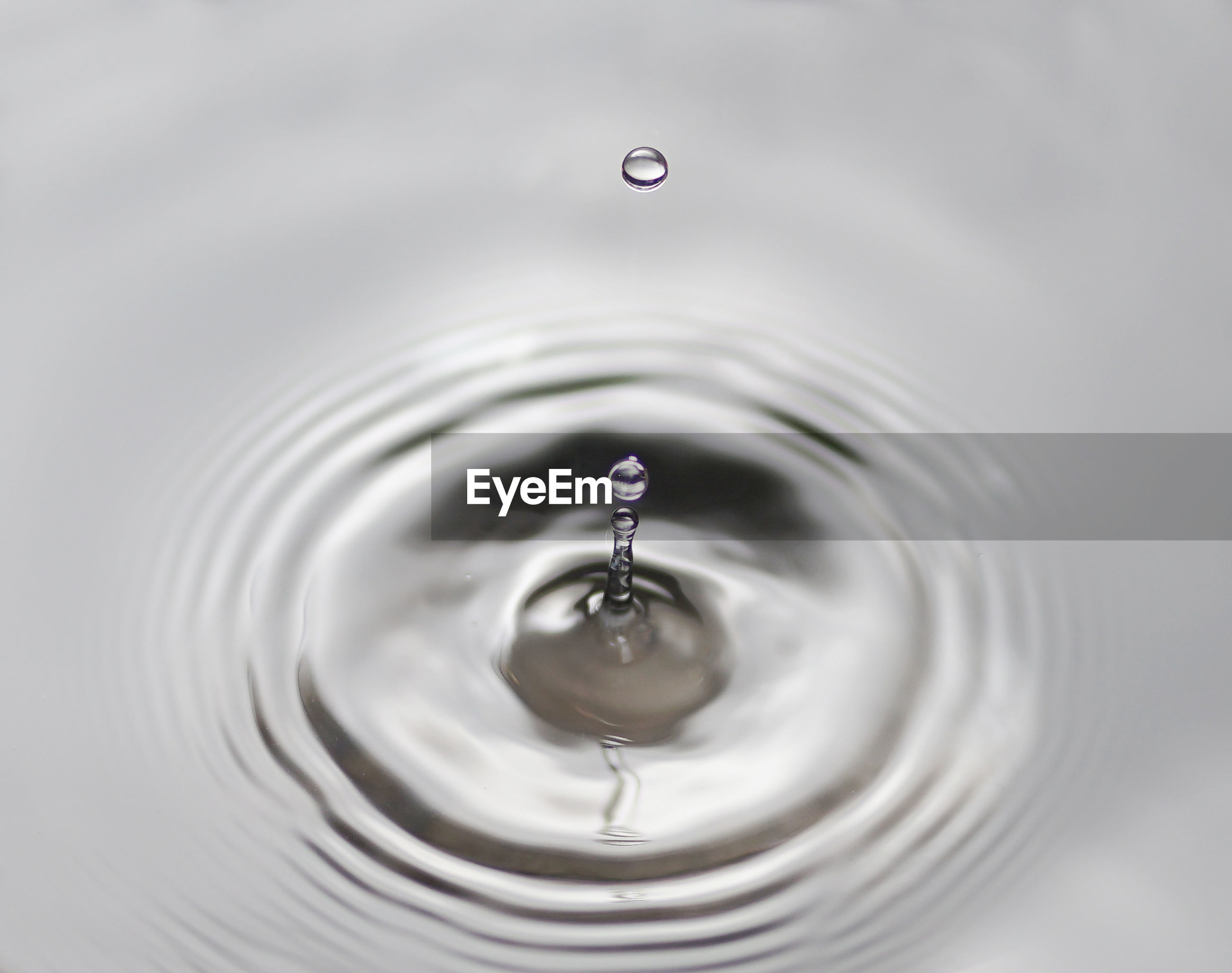 CLOSE-UP OF DROP FALLING ON WATER IN DRINKING GLASS