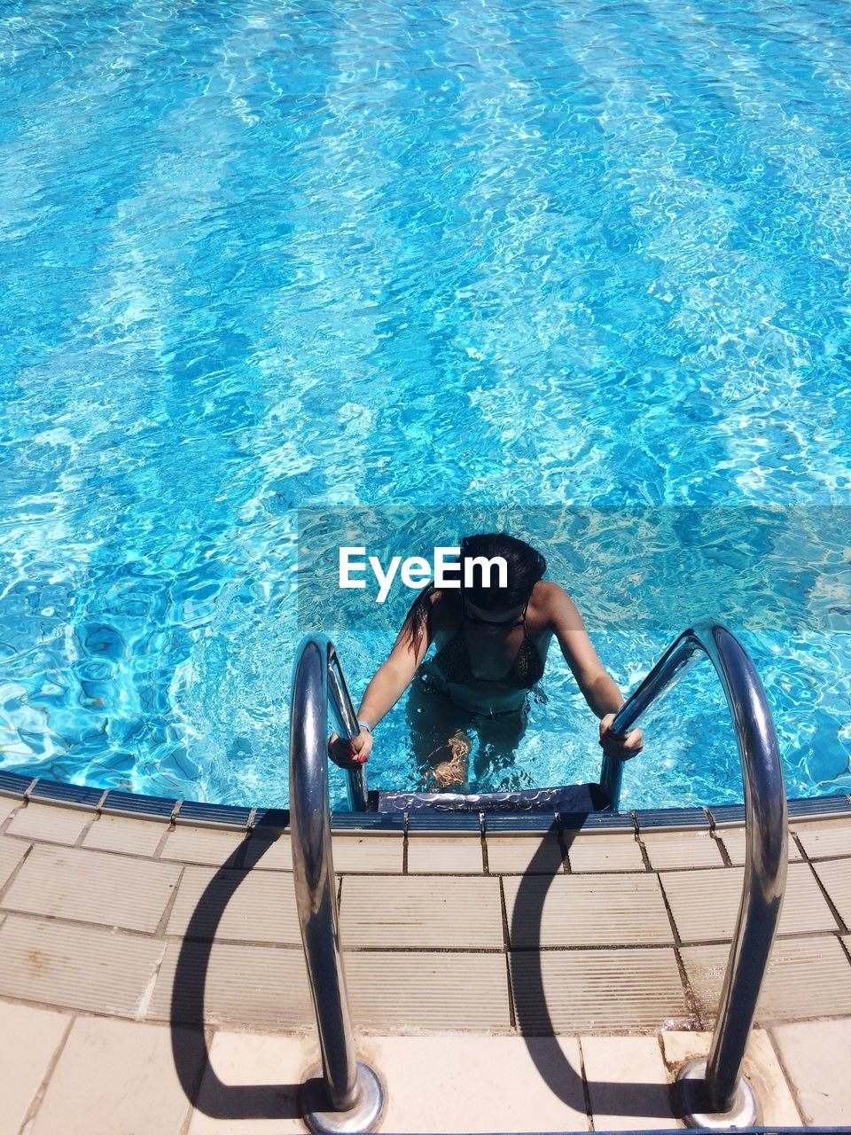 High angle view of woman on ladder in swimming pool