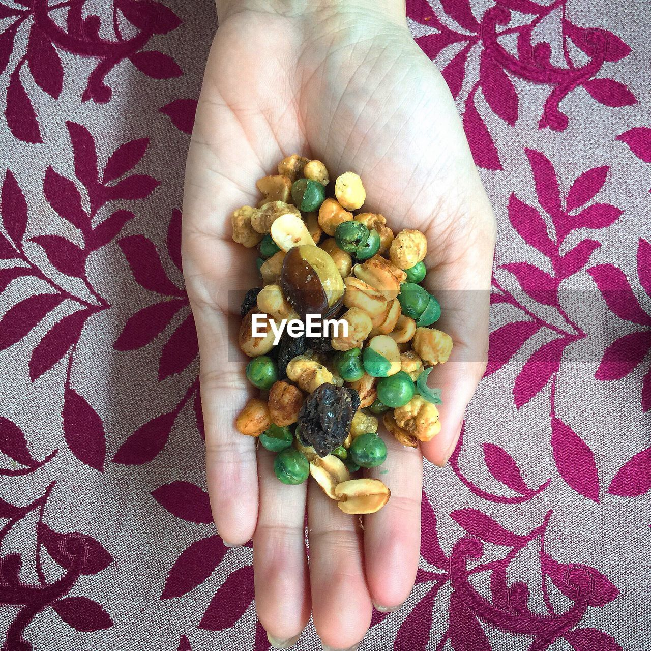 Directly Above Shot Of Woman Holding Roasted Nuts At Table