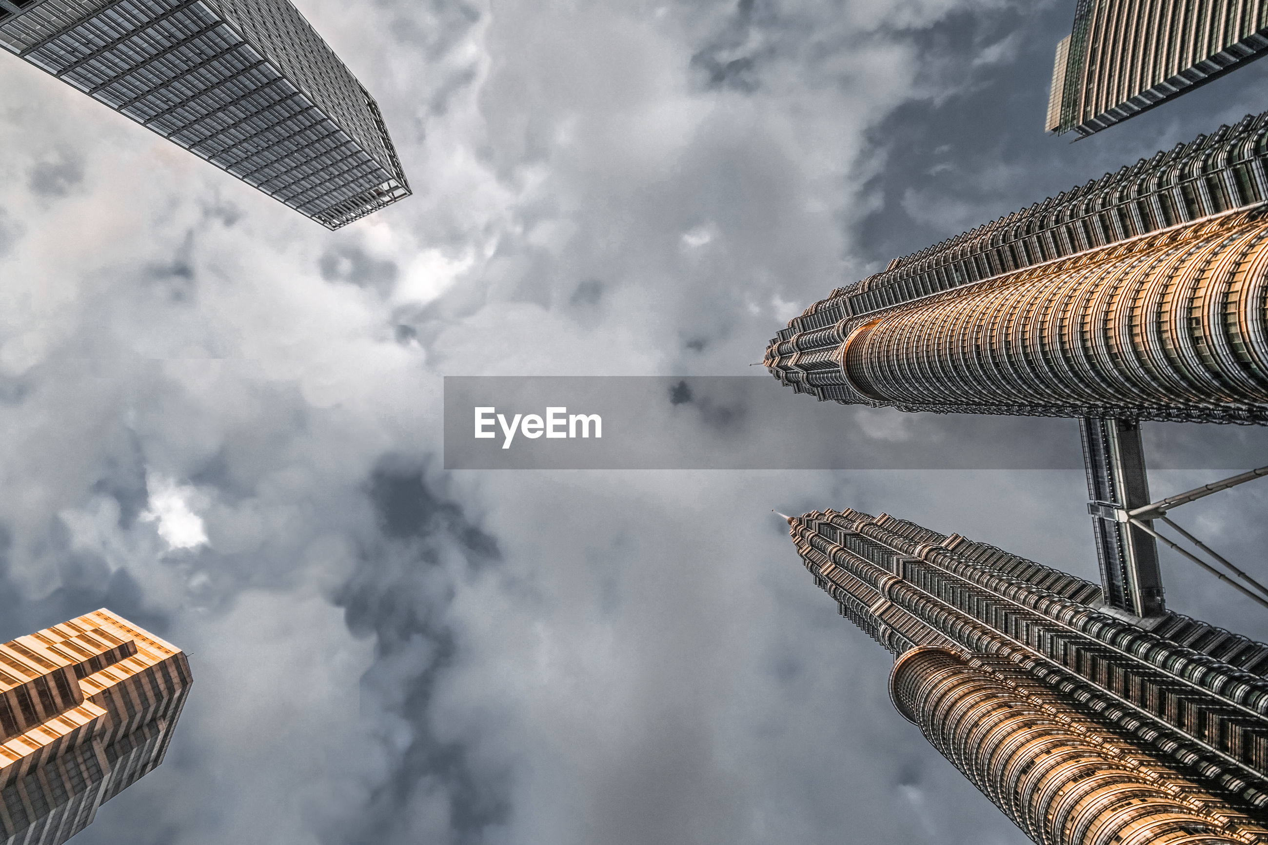 LOW ANGLE VIEW OF BUILDINGS IN CITY AGAINST CLOUDY SKY