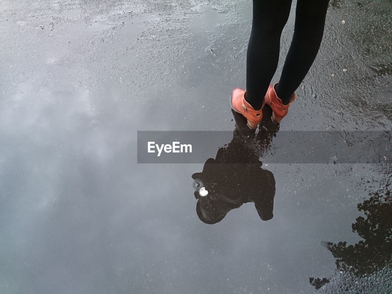 Woman standing in puddle