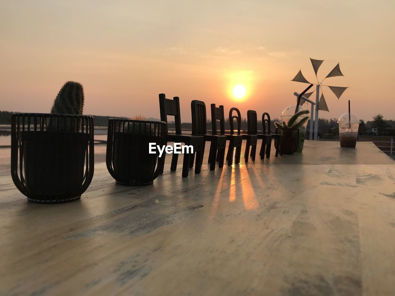 sunset, sky, water, scenics - nature, beauty in nature, nature, no people, orange color, reflection, sea, tranquil scene, sun, tranquility, wood - material, waterfront, outdoors, beach, non-urban scene, land, wooden post