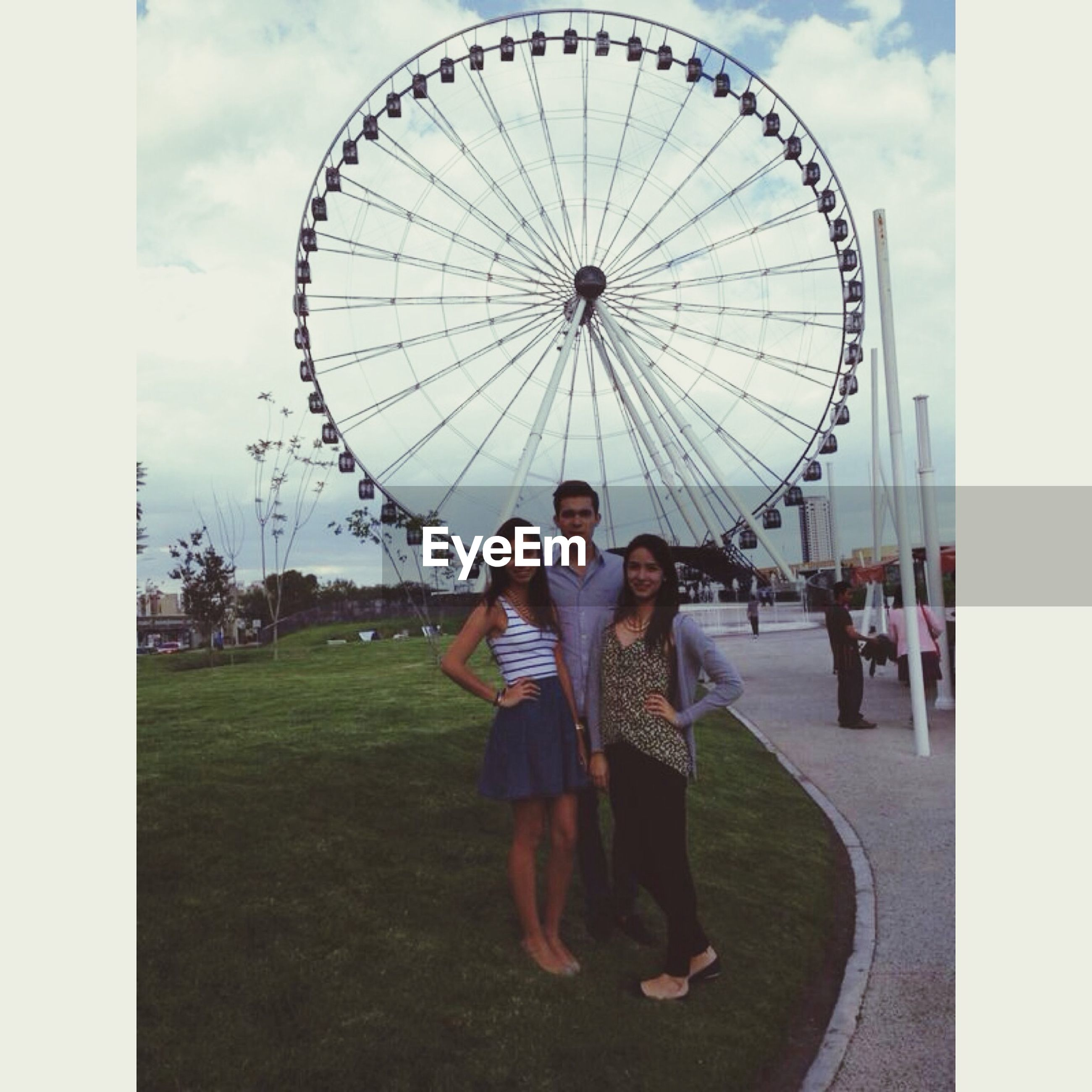 leisure activity, lifestyles, amusement park, transfer print, fun, full length, enjoyment, ferris wheel, amusement park ride, arts culture and entertainment, childhood, casual clothing, auto post production filter, sky, circle, standing, day, playing