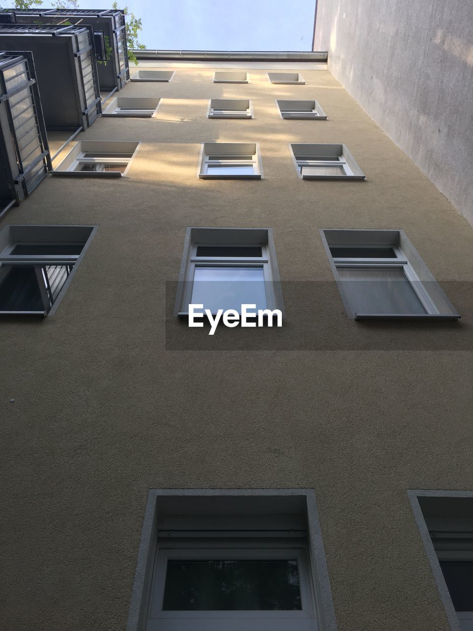 built structure, architecture, low angle view, building exterior, window, building, residential district, day, no people, outdoors, wall - building feature, wall, city, nature, in a row, glass - material, apartment, house, sunlight, facade, directly below