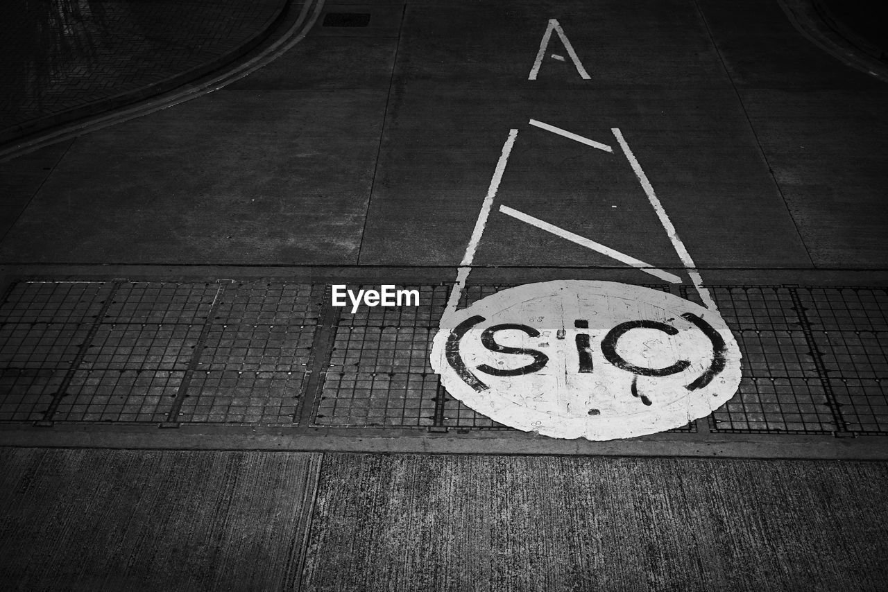 sign, communication, no people, symbol, road, number, road sign, day, high angle view, circle, guidance, geometric shape, road marking, information, marking, transportation, text, shape, indoors, direction