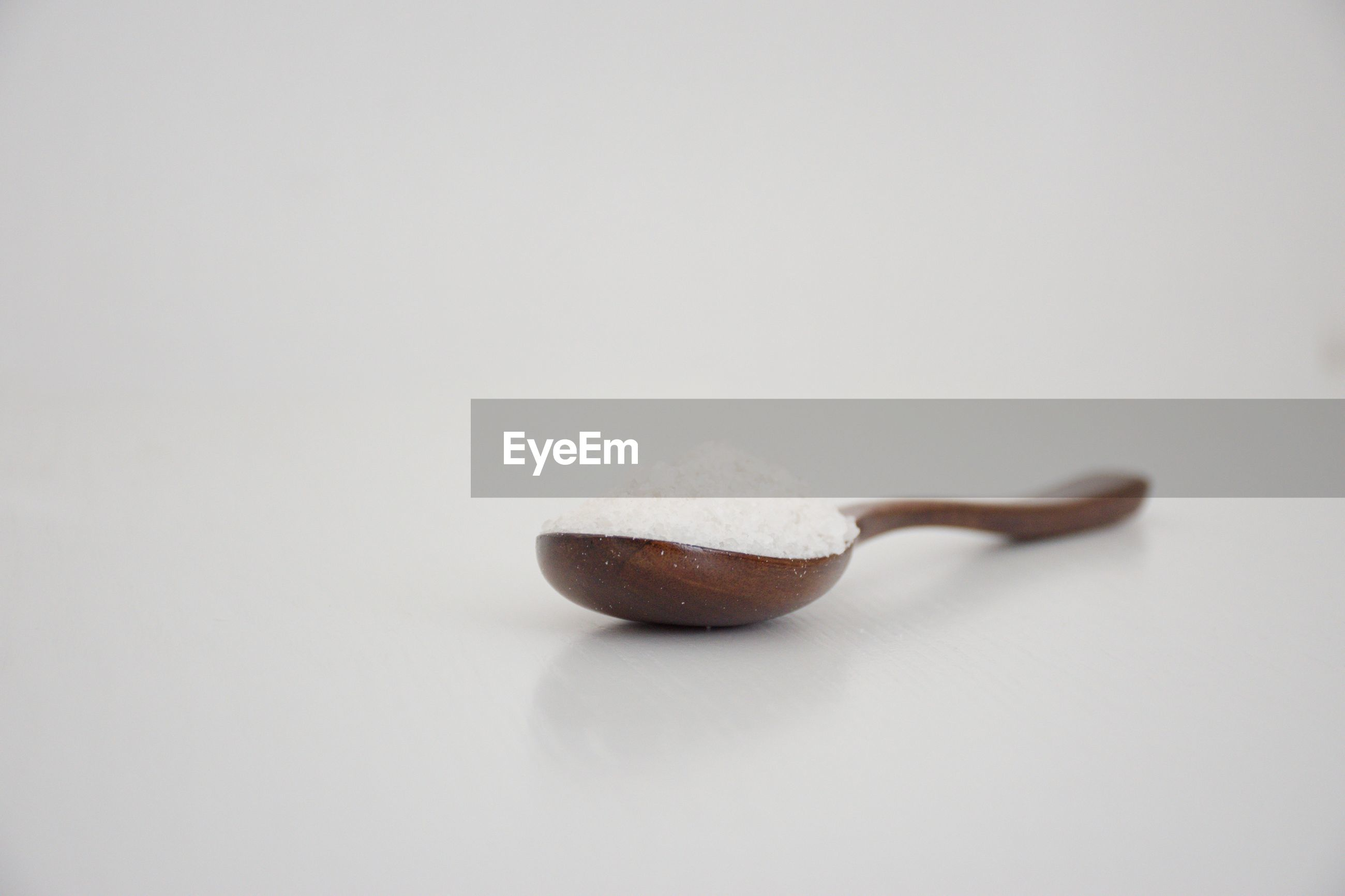 Wooden spoon with salt on the white background