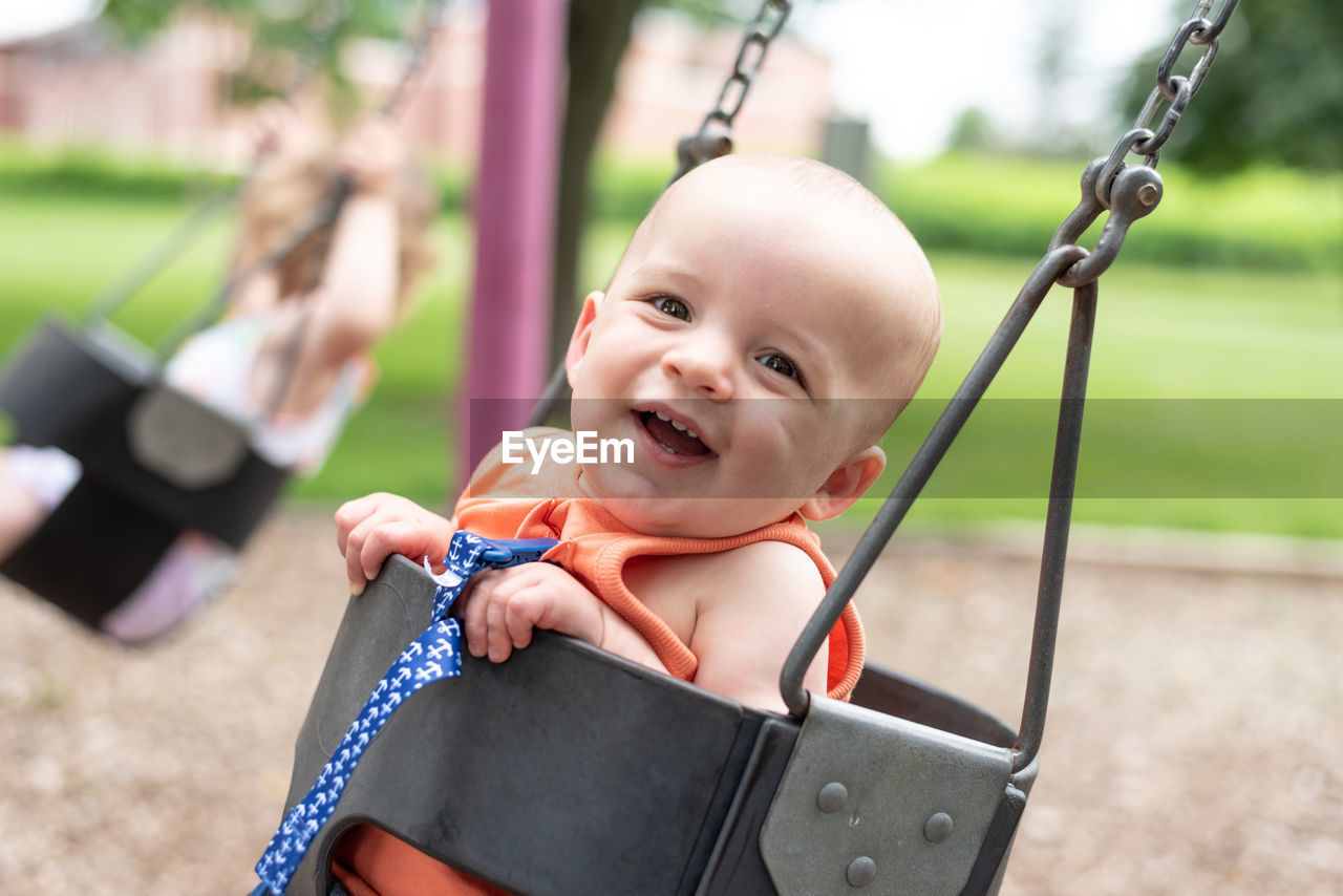 Portrait of boy sitting in swing at playground