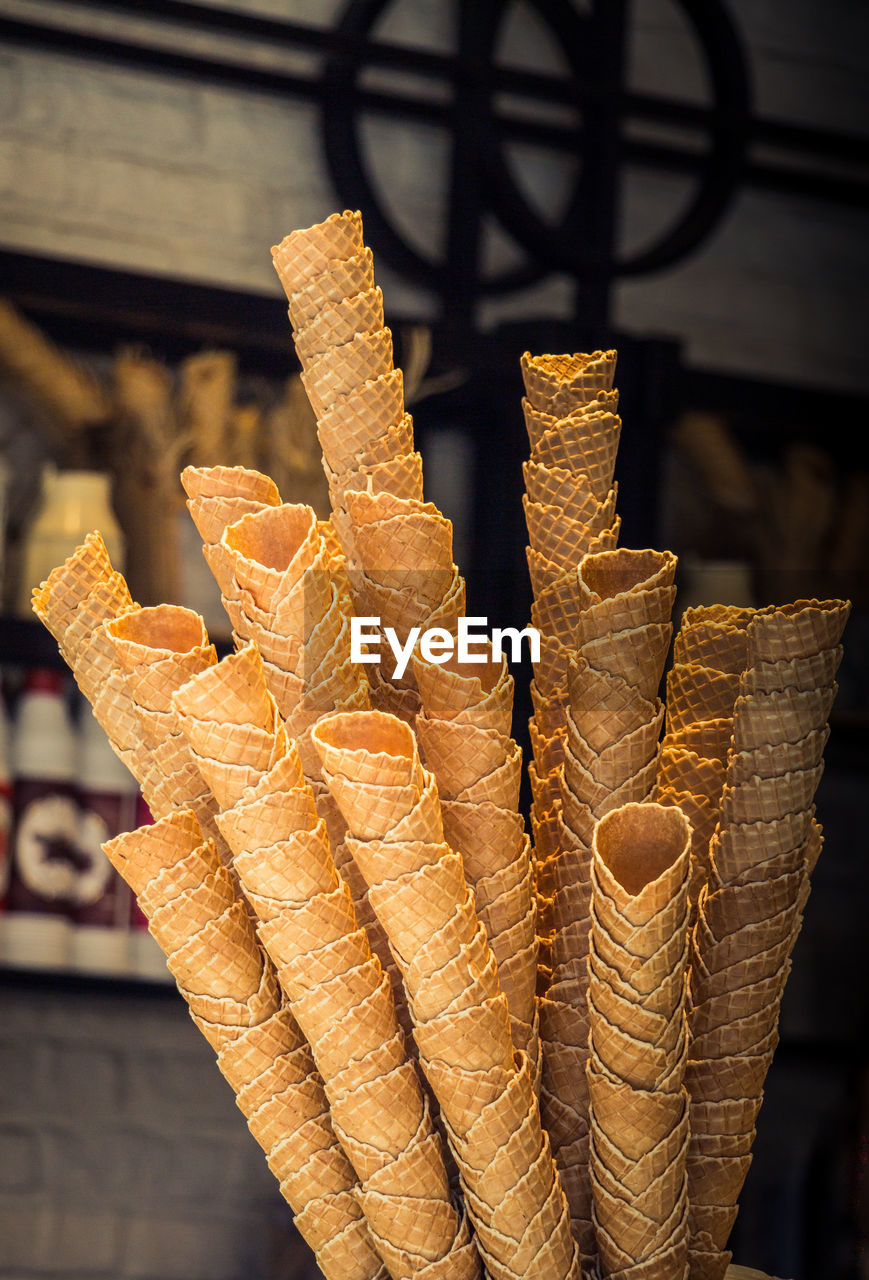 food, food and drink, freshness, focus on foreground, close-up, no people, still life, retail, for sale, cone, market, day, store, stack, ice cream cone, ready-to-eat, indoors, business, market stall, brown, snack, temptation