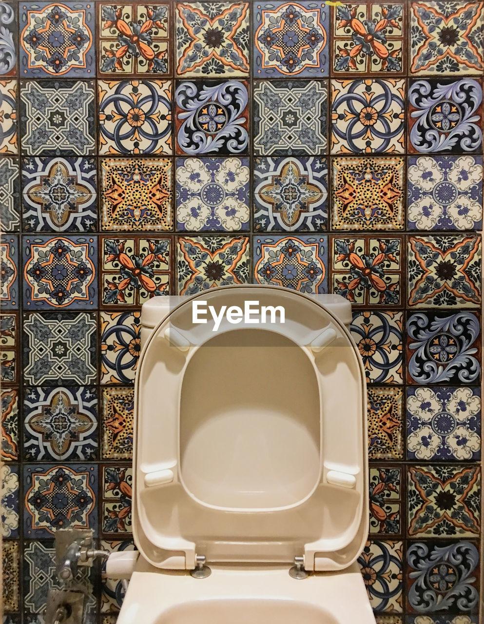 Toilet bowl against tiled wall